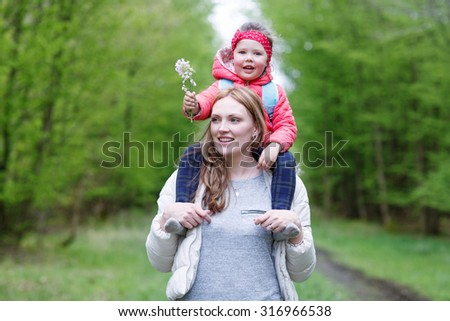 Beautiful mother carrying little girl on shoulders. Happy family of two, young smiling woman and her cute toddler daughter enjoying beautiful day in the forest - stock photo
