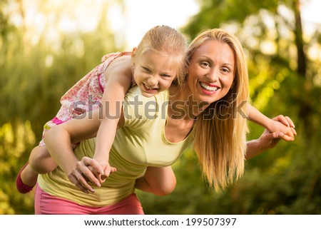 Beautiful mother giving her cute little girl piggyback and smiling in the park