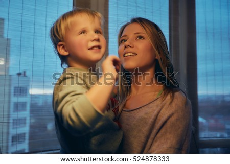 beautiful mother holds a baby son, large window in the background, family night, holiday