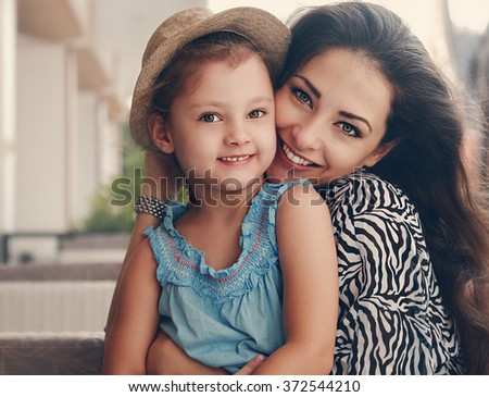 Beautiful mother hugging her cute daughter with happy smiling. Closeup toned portrait