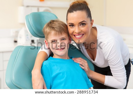 beautiful mother hugging her son in dentist office - stock photo