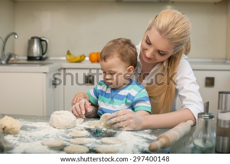 Beautiful mother is sitting at the table in the kitchen. She is holding her small son on her knees and smiling. They are baking pastry with interest. There is copy space in left side - stock photo