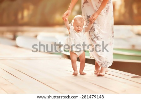 beautiful mother is walking on the pier with her little baby girl daughter with first steps - stock photo