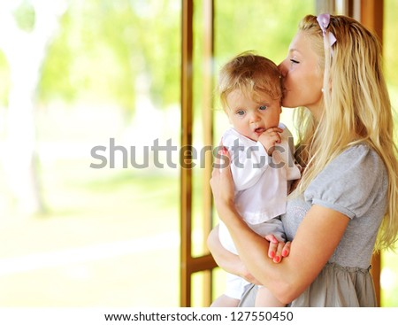 Beautiful mother kissing her adorable little son outdoors - stock photo