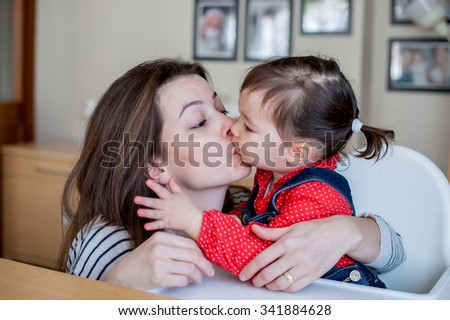 beautiful mother kissing her eighteen month daughter - stock photo