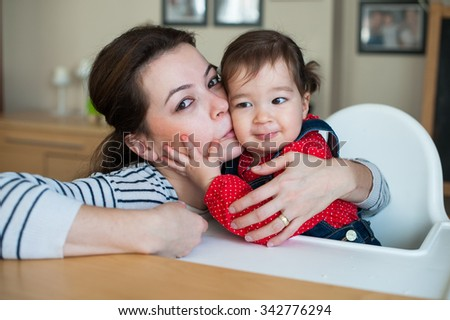 beautiful mother kissing her eighteen month daughter. - stock photo