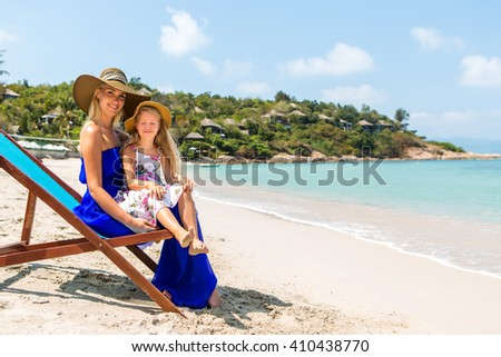 Beautiful mother lady in blue dress and beach straw hat with her pretty blonde cute daughter. Woman in a beach chair, little lady close her eyes. Happy family on the shore. Happy mothers day. - stock photo