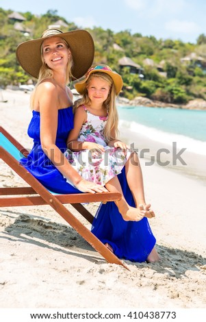 Beautiful mother lady in blue dress and beach straw hat with her pretty blonde cute daughter. Woman in a beach chair, little girl smile to the camera. Happy family on the beach. Happy mothers day.