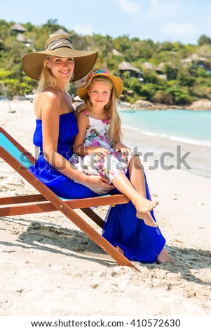 Beautiful mother lady in blue dress and beach straw hat with her pretty blonde cute daughter. Woman in a beach chair and little girl smile to the camera. Happy family on the beach. Happy mothers day. - stock photo