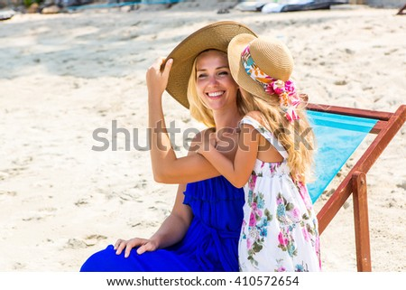 Beautiful mother lady with her pretty blonde cute daughter. Woman sitting in a beach chair and smile. Little girl say something to her ear. Happy family on the beach. Happy mothers day. - stock photo