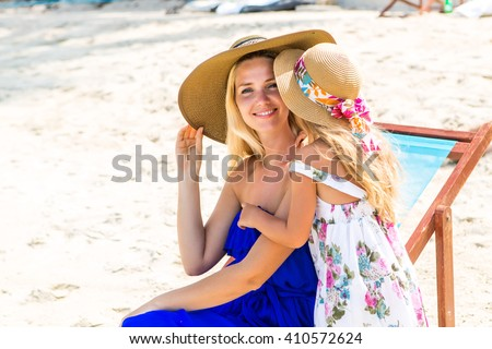 Beautiful mother lady with her pretty blonde cute daughter. Woman sitting in a beach chair, smile and look to camera. Little girl say something to her ear. Happy family on beach. Happy mothers day. - stock photo