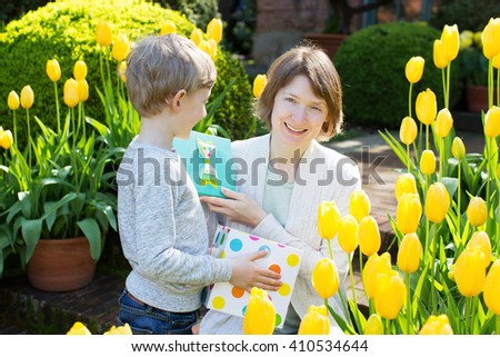 beautiful mother opening her mother's day present received from her little son in the park at springtime