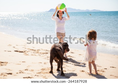 Beautiful mother playing ball with her daughter and dog at the beach on a sunny day