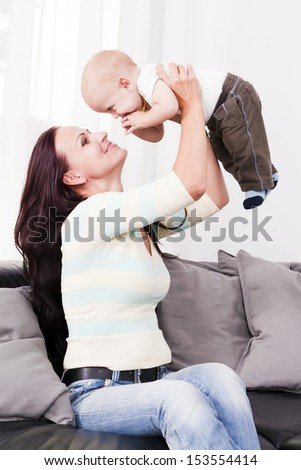 Beautiful mother playing his beby the home. - stock photo