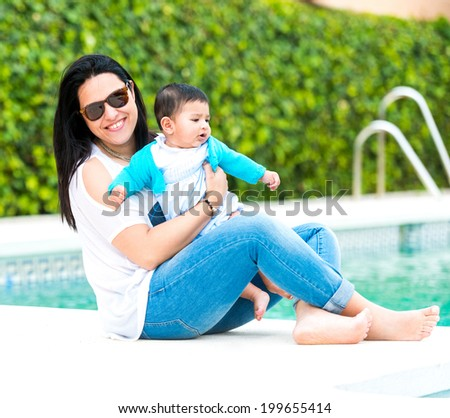 beautiful mother playing with baby boy near the swimming pool on a sunny summer day - stock photo