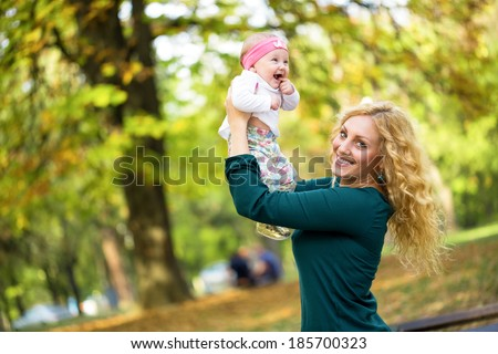 Beautiful mother playing with baby in park