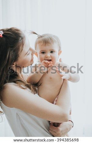 Beautiful mother portrait playing with her cute little girl in a white room