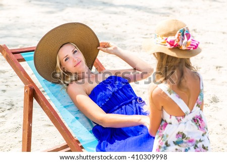 Beautiful mother relaxing in a beach chair. Her cute blonde daughter in dress and beach straw hat talk to she. Woman look to the camera. Happy family on the shore. Happy mothers day. - stock photo