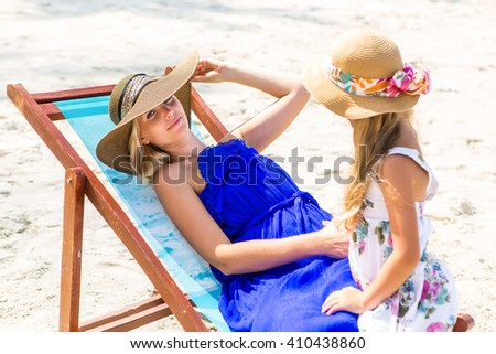 Beautiful mother relaxing in a beach chair. Her cute blonde daughter in dress and beach straw hat talk to she. Woman look to the camera and touch her hat. Happy family on the shore. Happy mothers day. - stock photo