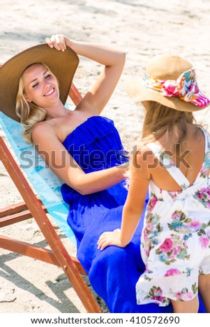 Beautiful mother relaxing in a beach chair. Her cute blonde daughter in dress and beach straw hat talk to she. Woman smile to little girl. Happy family on the shore. Happy mothers day. - stock photo