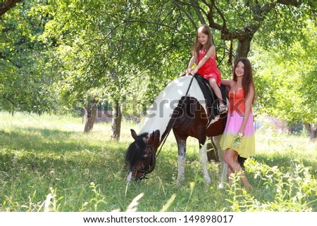 Beautiful mother rolls the smiling little girl on a pony in a summer park