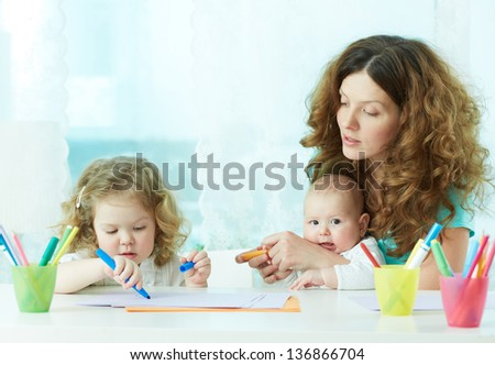 Beautiful mother showing her children how to draw - stock photo