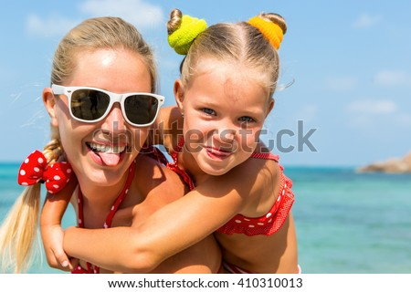 Beautiful mother sunglasses with cute little daughter on her back. Two in red bikini. Woman and little lady show tongue, smile and looking to camera. Happy family on the sea shore. Happy mothers day.