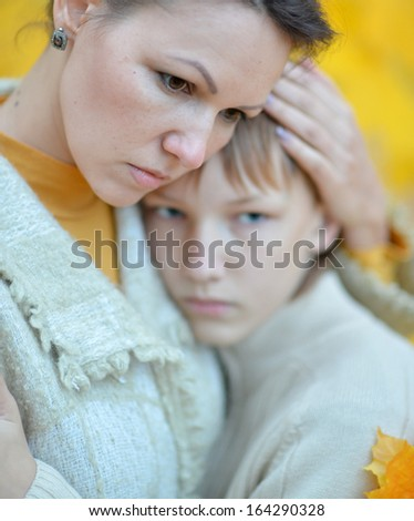 Beautiful mother with a boy on a walk during the fall of the leaves in the park - stock photo