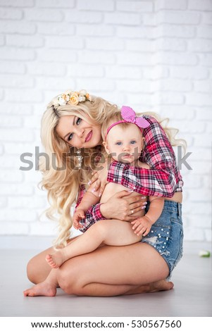Beautiful mother with a young daughter in her arms. Photographed in a light tone in the interior of a white studio. The beauty of motherhood, family happiness, a woman with white wavy hair