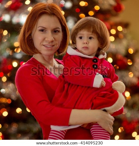 Beautiful mother with baby girl near a Christmas tree - stock photo