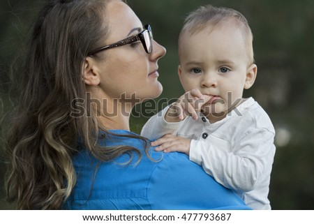 Beautiful mother with her child having fun outdoors.