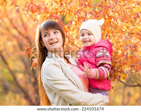 beautiful mother with kid girl outdoors in autumnal park