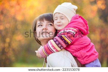 beautiful mother with kid girl outdoors over golden autumn background - stock photo