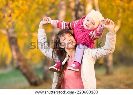 beautiful mother with kid girl walking outdoors in autumnal park