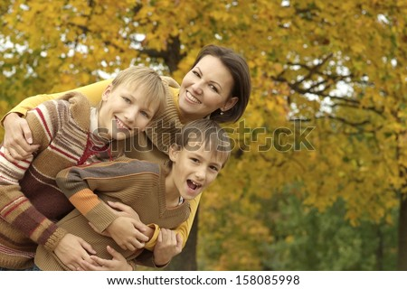 beautiful mother with sons on the air, even so early in the autumn - stock photo