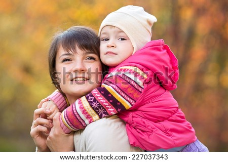 beautiful mother with toddler girl outdoor in fall