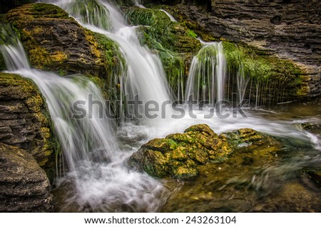 Beautiful motion blurred waterfall flowing from mossy rocks  - stock photo