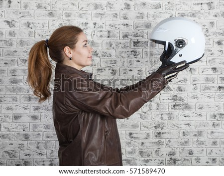 Beautiful motorcyclist selects white open helmet while holding in stretching arms, brick wall background, side view