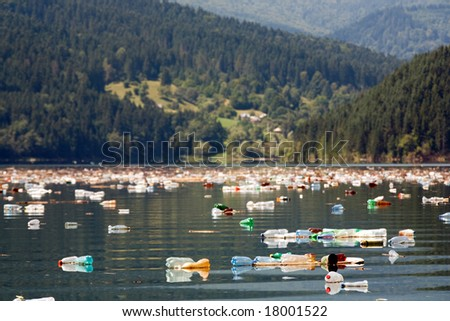 beautiful mountain and lake landscape with big pollution of plastic bottles - stock photo