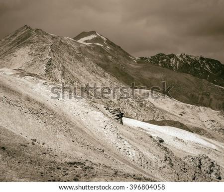 Beautiful mountain landscape near the Tso Moriri lake and Karzok village in Rupshu valley against the background of cloudly sky - Tibet, Ladakh, Himalayas, Jammu and Kashmir, India (stylized retro) - stock photo