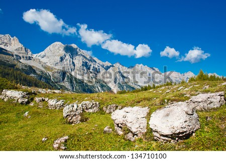 Beautiful mountain landscape. There are big stones in the foreground. Ridge goes over the horizon. There is a forest at the foot of the mountains. The sky is blue and cloud.