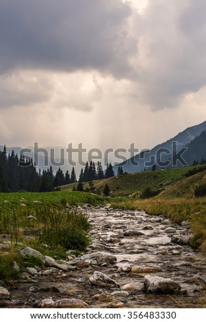 Beautiful mountain scenery in the Transylvanian Alps with storm clouds, in summer - stock photo