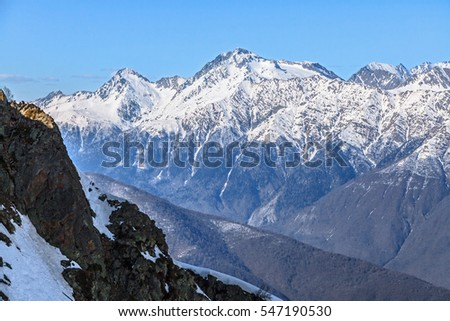 Beautiful mountain scenic winter landscape of the Main Caucasus ridge with snowy peaks and blue sky on a sunny day