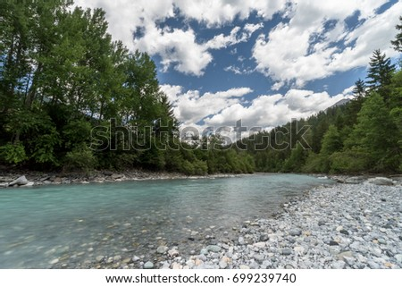 beautiful mountain stream and a rocky beach with green forest and sky with clouds behind in the Engadin in the Swiss Alps near Scuol on a summer day