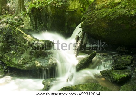 beautiful mountain stream waterfalls in moss covered forest - stock photo