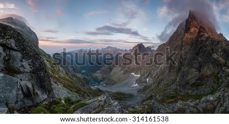 Beautiful mountains at sunset with pink clouds and a lake in the valley, landscape