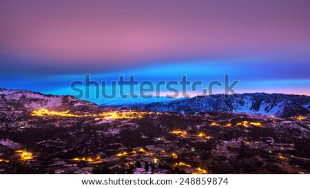 Beautiful mountains landscape, amazing pink and blue sky over mountainous glowing city, beauty of nighttime, winter holidays concept - stock photo