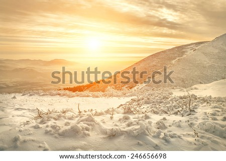 Beautiful mountains view at winter under sunset sky. - stock photo