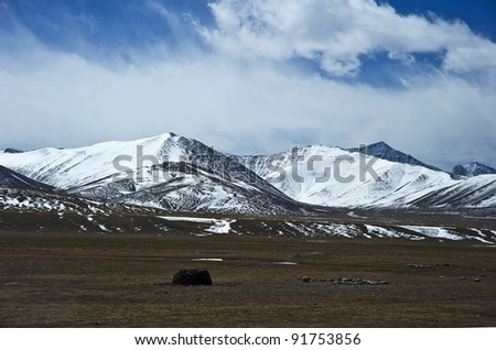 beautiful mountains view covered by heavy snow with blue sky and white cloud in tibet China