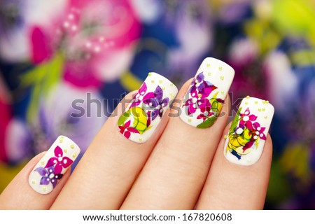 Beautiful multicolored flowers on a white lacquer on the nails on a multicolored background. - stock photo